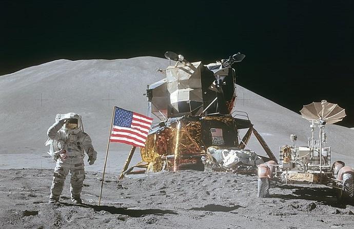 """האסטרונאוט ג'יימס אירווין מצדיע לדגל ארה""""ב במהלך משימת אפולו 15, על רקע רכב הנחיתה הירחי מתוצרת חברת גראמן (לימים נורת'רופ גראמן). קרדיט: נאס""""א"""