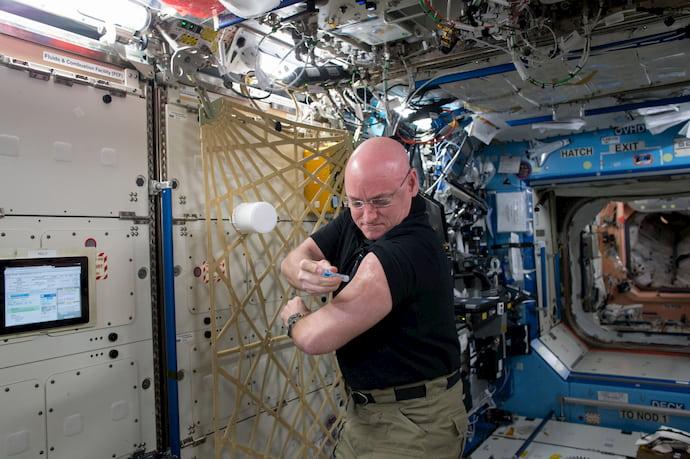 סקוט קלי מזריק לעצמו חיסון נגד שפעת במסגרת ניסוי שנערך בתחנת החלל ב-2015. קרדיט: NASA