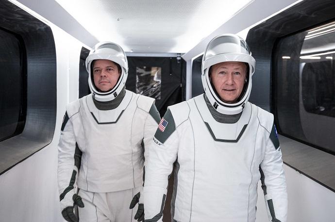 """בוב בנקן ודאג הארלי הולכים בזרוע המחברת למגדל השיגור. אם החליפות שלהם מזכירות לכם סרט הוליוודי, זה לא במקרה. קרדיט: נאס""""א"""