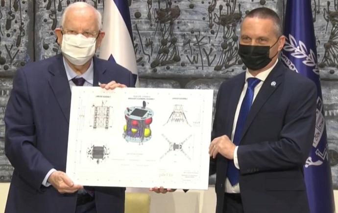 שר המדע והטכנולוגיה, יזהר שי, ונשיא המדינה, ראובן (רובי) ריבלין אוחזים בשרטות החללית בראשית 2