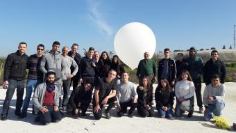 קבוצת תלמידים על רקע אחת מאבני הדרך בפרויקט, הפסאודו-לוויין
